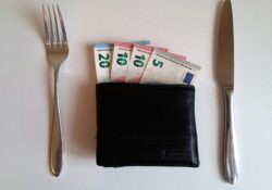 Wallet on a dinner table. Money is showing from the wallet. What is the value of food?