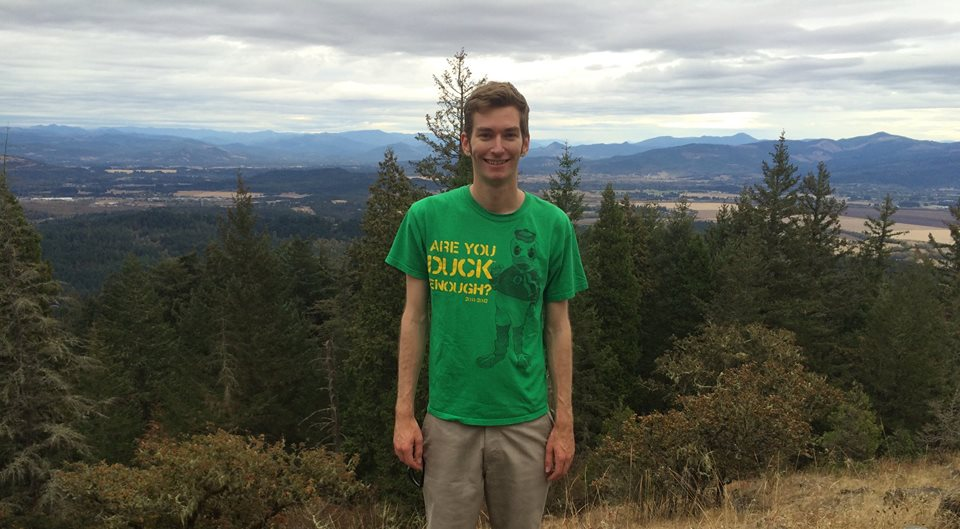 "Elliott Killian ElliottKillian in Eugene Oregon with Forests behind him after a hike. He is wearing a University of Oregon Shirt on that says""Are you duck enough"" And has a U of O Duck on it."