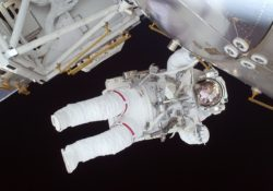 An Astronaut floating in space next to a space craft. The Astronaut is in a space suit and is almost horizontal