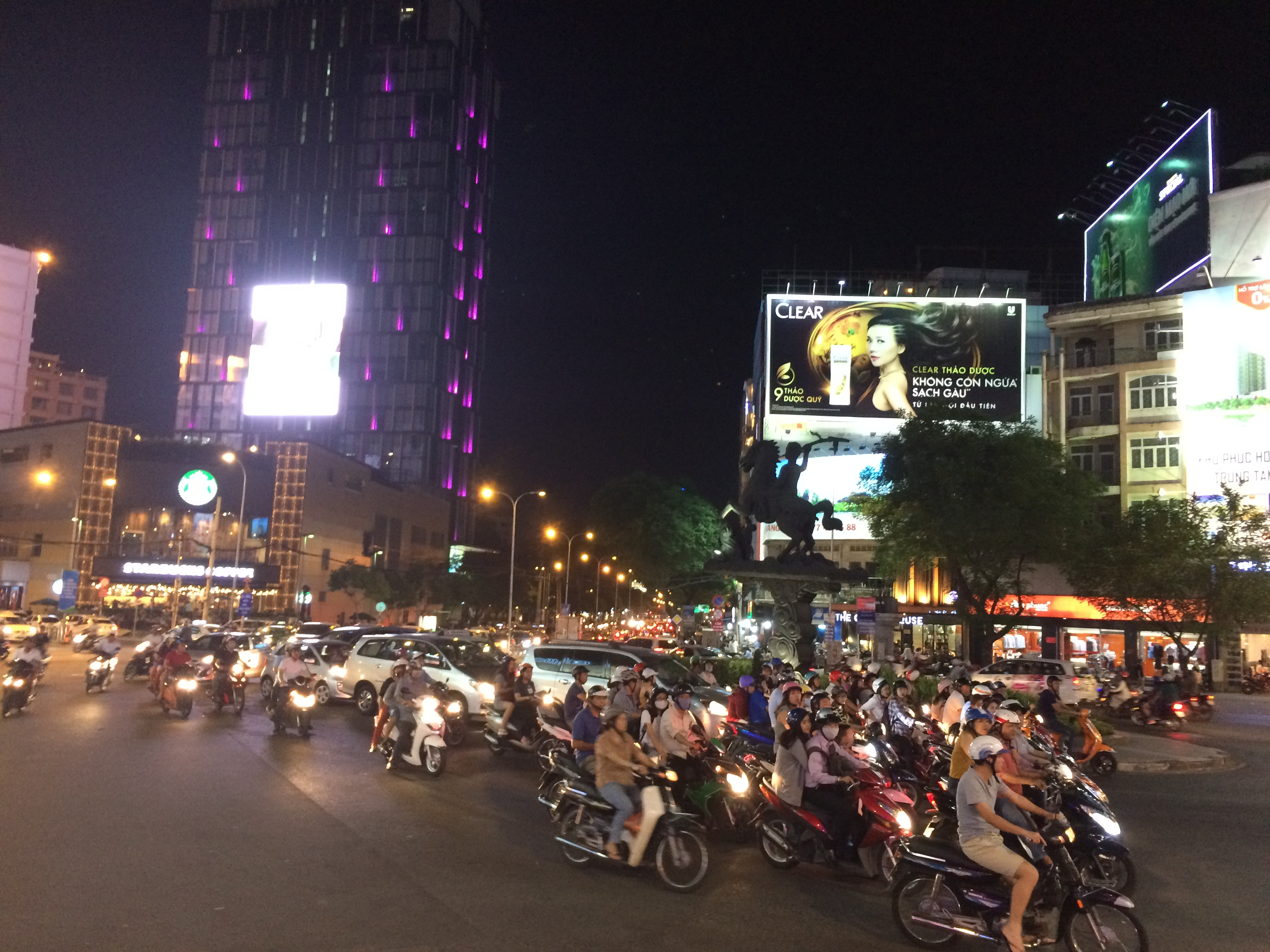 Ho Chi Minh city at night. The street is filled with motorbikes.